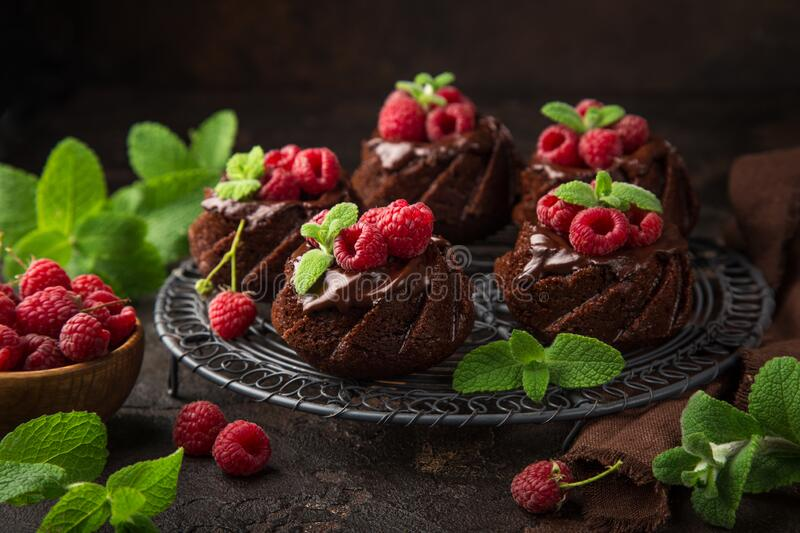 Delicious chocolate muffins with chocolate topping and fresh raspberry. On dark background, selective focus stock photography