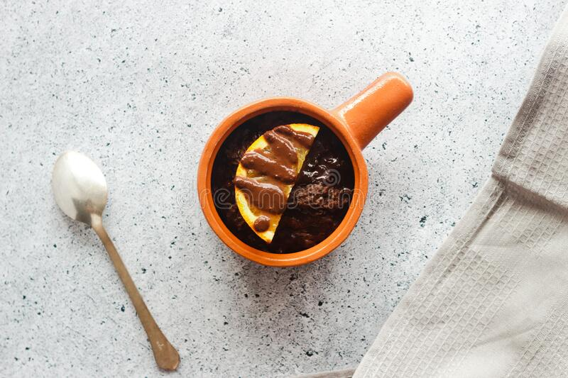 Delicious chocolate pudding with orange. Potted pudding on the table stock images