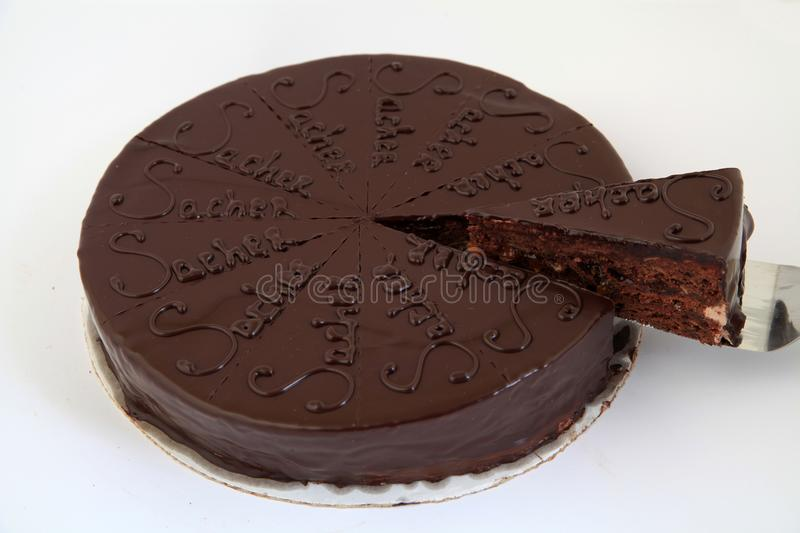 Delicious chocolate sacher cake with one piece cut from the whole cake royalty free stock image