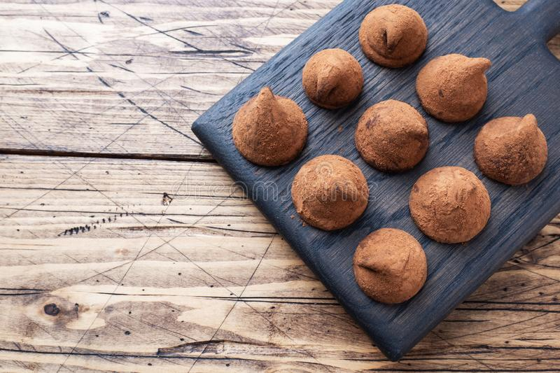 Delicious chocolate truffles sprinkled with cocoa powder on a wooden stand. Wooden background. Copy space royalty free stock photo