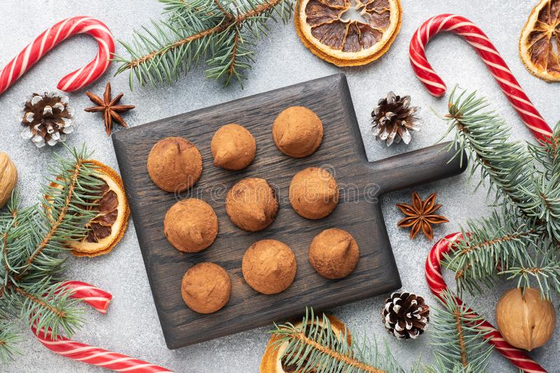 Delicious chocolate truffles sprinkled with cocoa powder on a wooden stand. Christmas tree scenery concept royalty free stock photo