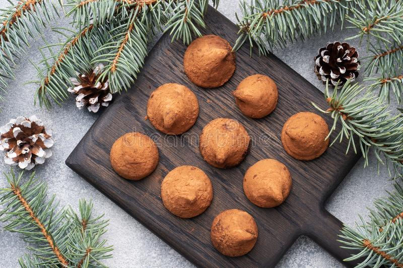 Delicious chocolate truffles sprinkled with cocoa powder on a wooden stand. Christmas tree scenery concept royalty free stock photography