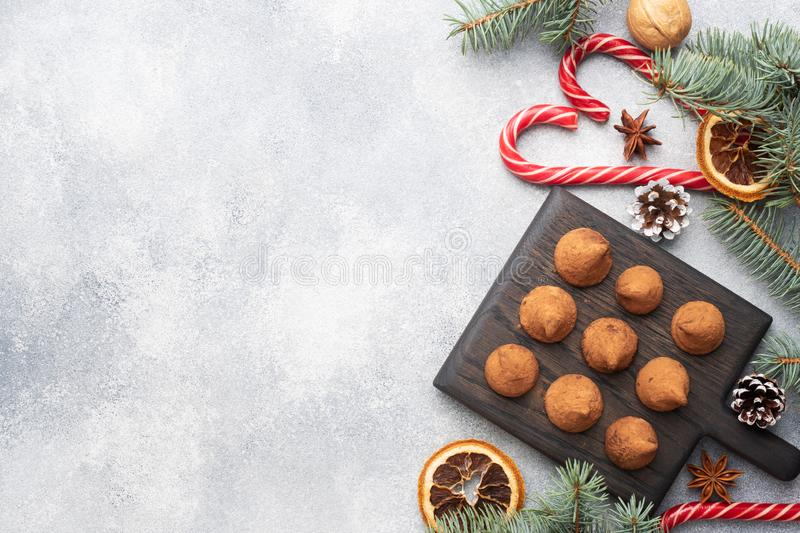 Delicious chocolate truffles sprinkled with cocoa powder on a wooden stand. Christmas tree scenery concept. Copy space royalty free stock photos