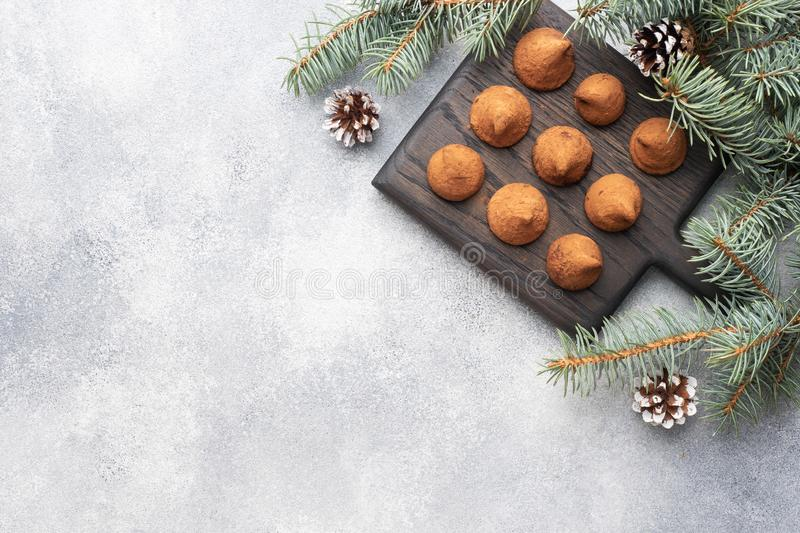 Delicious chocolate truffles sprinkled with cocoa powder on a wooden stand. Christmas tree scenery concept. Copy space royalty free stock photo