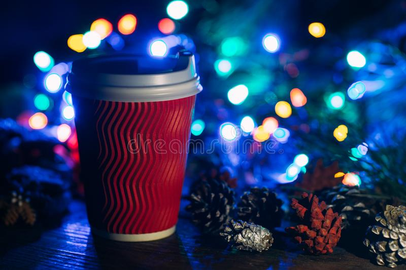 Delicious Christmas celebration with latte. Close up cup of warm energy drink and strobila decoration on defocused fairy lights background. Cozy xmas evening stock images