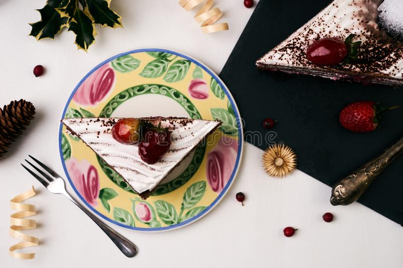 Delicious Christmas dessert. Cake with fresh strawberries . Slice of cake with souffle, strawberrie cream and chocolate crumbs with christmas decorations, fir royalty free stock photos