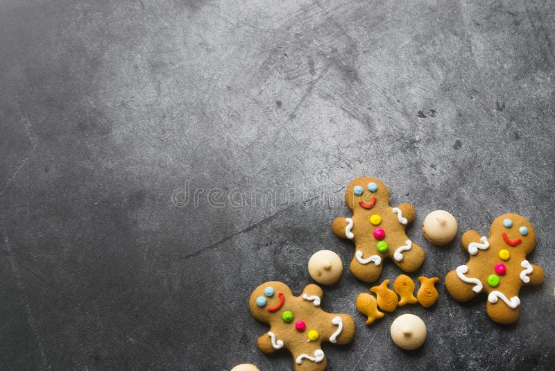 Delicious Christmas gingerbread men.Christmas baking ingredients and supplies on dark background.Postcard. Congratulation.Cooking stock photo
