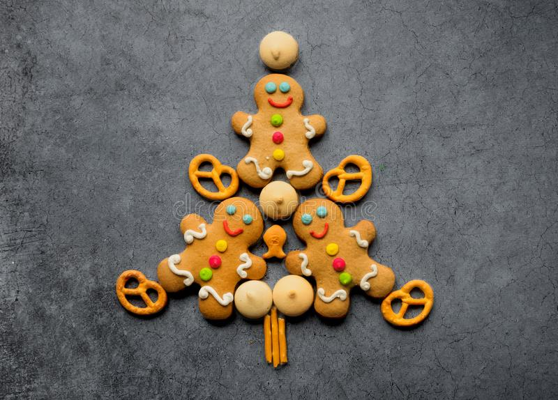 Delicious Christmas gingerbread men in the form of a Christmas tree. Christmas baking ingredients and supplies on dark background stock images