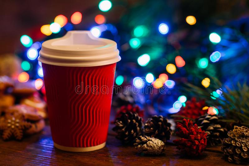 Delicious Christmas with take away latte. Close up cup of warm energy drink and strobila decoration on festive fairy lights background. Cozy xmas evening in royalty free stock photography