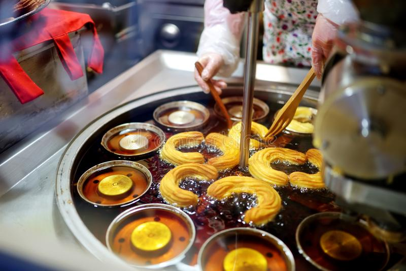 Delicious churros being baked at one of the stalls on the Christmas market in Vilnius, Lithuania stock image