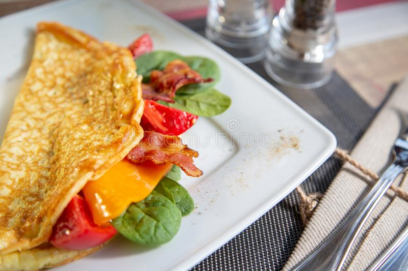 Delicious close up omelette with cheese ,grill tomato.ham,crispy becon and salad stock photo