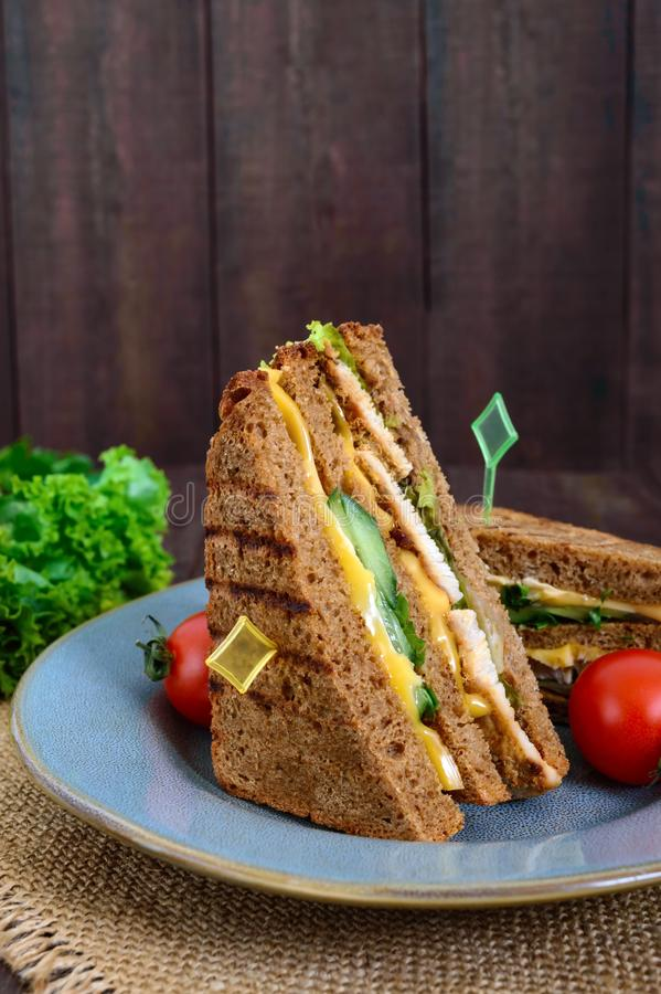 Delicious club-sandwich with rye bread, chicken, cheese, cucumbers, greens. On a dark wooden background stock images