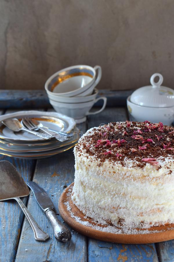 Delicious coconut layer cake - biscuit and cream on coconut cream, decorated with grated chocolate and candied rose petals. Coconut layer cake - biscuit and stock photos