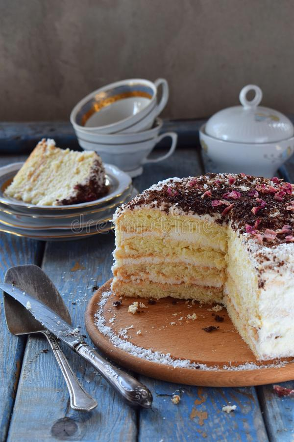 Delicious coconut layer cake - biscuit and cream on coconut cream, decorated with grated chocolate and candied rose petals. Coconut layer cake - biscuit and stock image