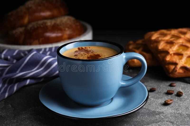 Delicious coffee and pastries on grey table. Delicious coffee and pastries on grey stock photo