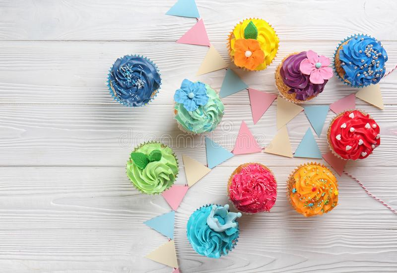 Delicious colorful cupcakes with party decor on white wooden background royalty free stock image