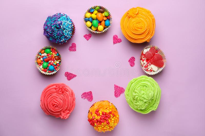 Delicious colorful cupcakes with sweets on color background royalty free stock photography