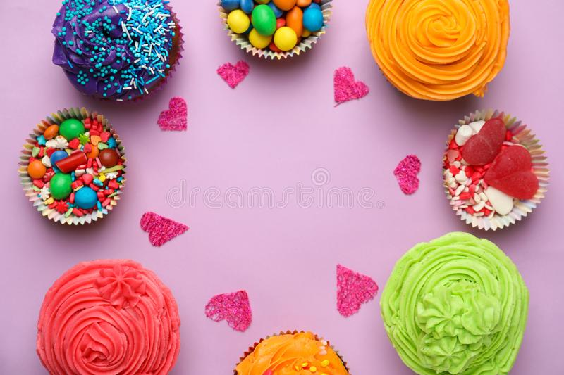 Delicious colorful cupcakes with sweets on color background royalty free stock image