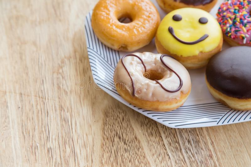 Donuts in box. Delicious colorful donuts in box on wooden background stock photography