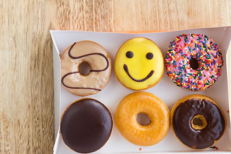 Donuts in box. Delicious colorful donuts in box on wooden background stock photos