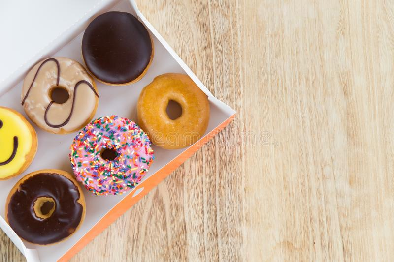 Donuts in box. Delicious colorful donuts in box on wooden background royalty free stock photos