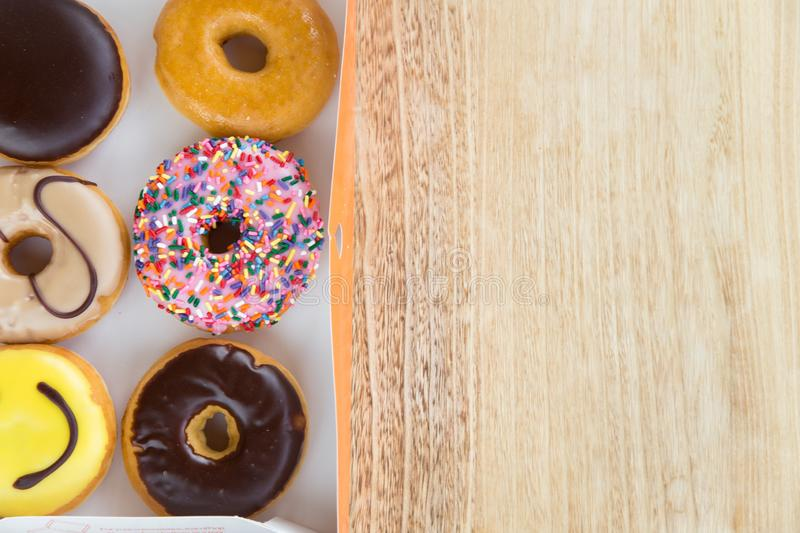 Donuts in box. Delicious colorful donuts in box on wooden background stock photo