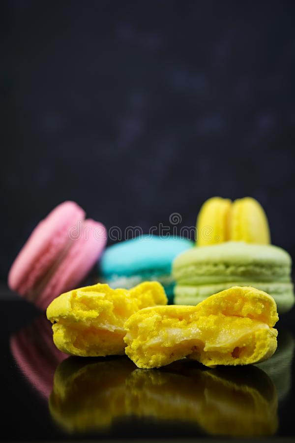 Delicious colorful macaron cakes on dark background.  stock photography