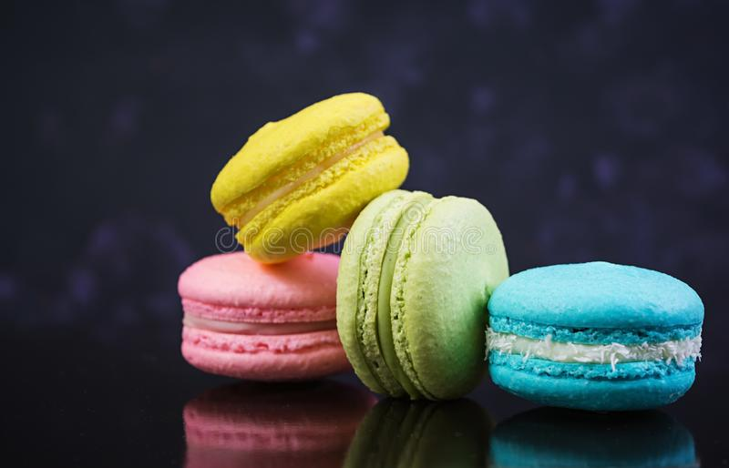 Delicious colorful macaron cakes on dark background.  stock photo