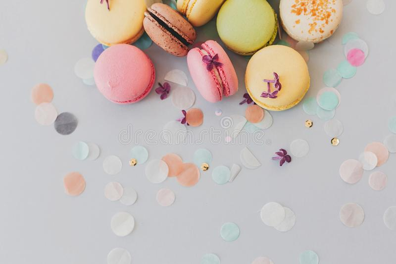 Delicious colorful macaroons on trendy pastel gray paper with li stock image
