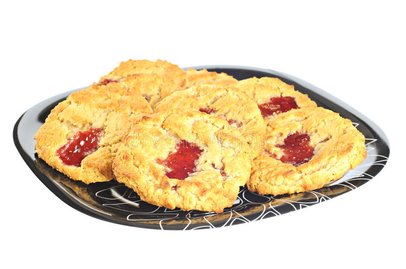 Delicious cookies with strawberry jam on a plate, on white background