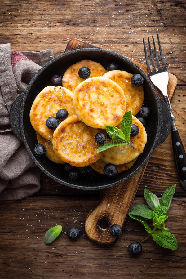 Delicious cottage cheese pancakes or syrniki with fresh blueberry in cast-iron pan on dark wooden rustic background, above view. T stock photo