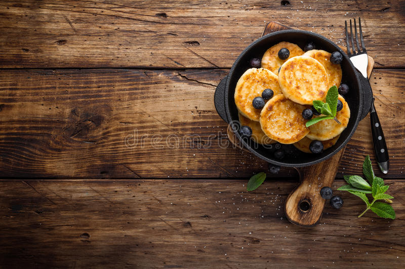 Delicious cottage cheese pancakes or syrniki with fresh blueberry in cast-iron pan on dark wooden rustic background, above view. T royalty free stock images