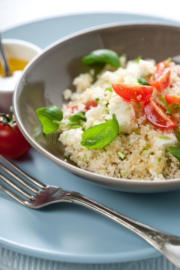 Delicious couscous dish. Delicious dish with fresh couscous salad and cherry tomatoes royalty free stock image