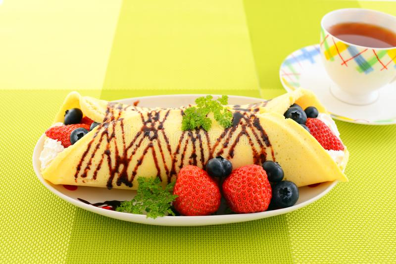 Delicious crepe. With fruits on the plate royalty free stock images