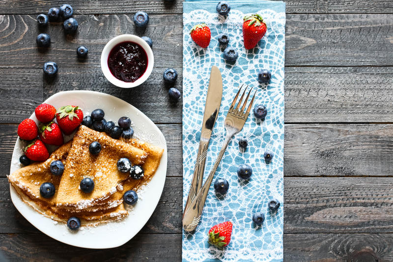 Delicious Crepes Breakfast with Dramatic light over a wood background. Delicious Crepes Breakfast with Dramatic light over a vintage wood background. An healthy royalty free stock photography