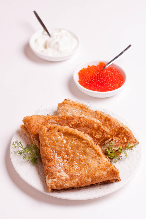 Delicious crepes with red caviar, dill and sour cream, isolated. On white, close up, vertical, top view stock image