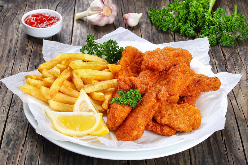 Delicious crispy chicken nuggets with fries stock photo
