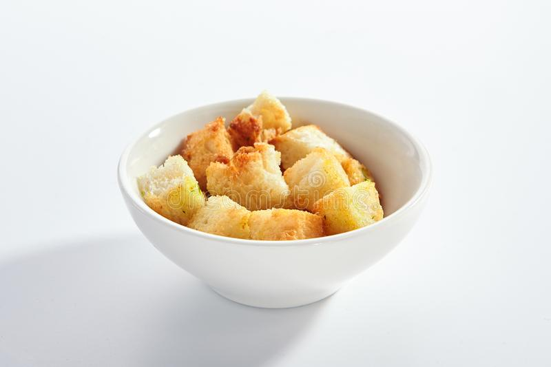 Delicious crunchy white bread croutons. Top view. Tasty vegan eating, homemade beer snack. Bowl with toasted appetizer isolated on background. Natural stock photography