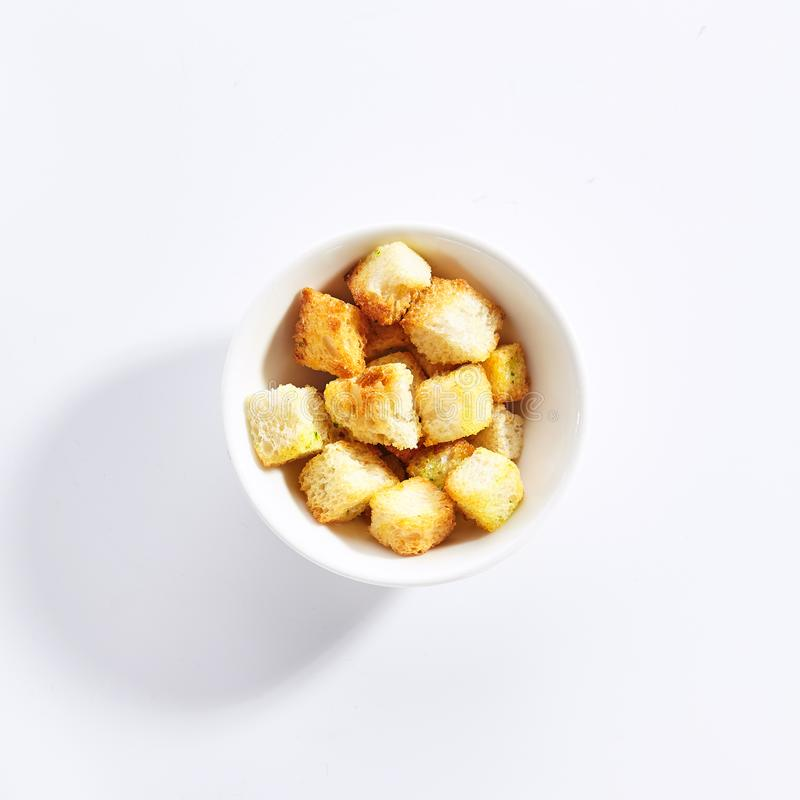 Delicious crunchy white bread croutons top view. Tasty vegan eating, homemade beer snack. Bowl with toasted appetizer isolated on background. Natural stock image