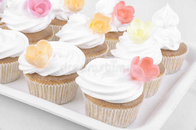 Delicious cup cakes with icing on top. And rose flowers stock photography