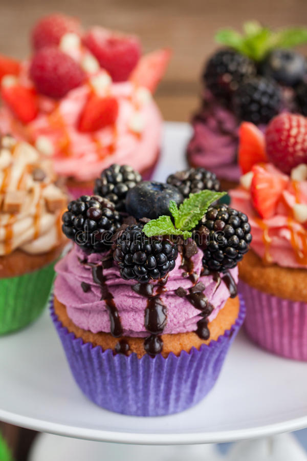 Delicious cupcake decorated with blueberry and blackberries stock photo