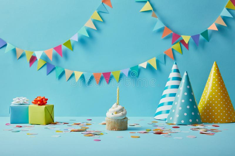 Delicious cupcake, party hats, confetti and gifts on blue background stock photo