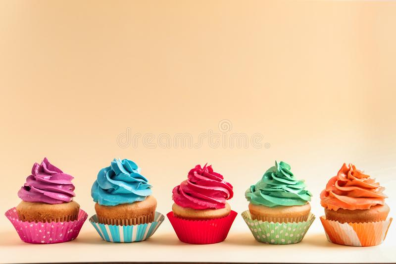 Delicious cupcakes on background. Delicious cupcakes on color background royalty free stock photography