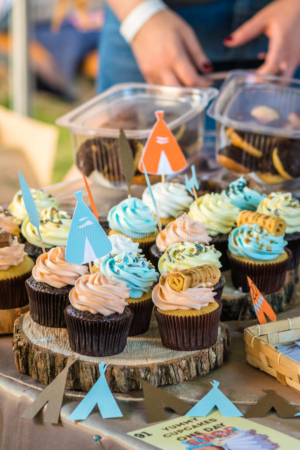 Delicious cupcakes with colored cream. On wooden stumps stock photo