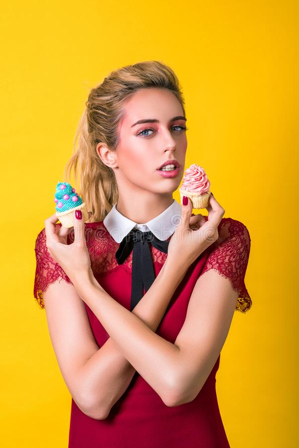 Delicious cupcakes. Fashion girl eating food, eating colorful cupcakes. Sensual woman in elegant dress. Fashion makeup, hairstyle royalty free stock photography