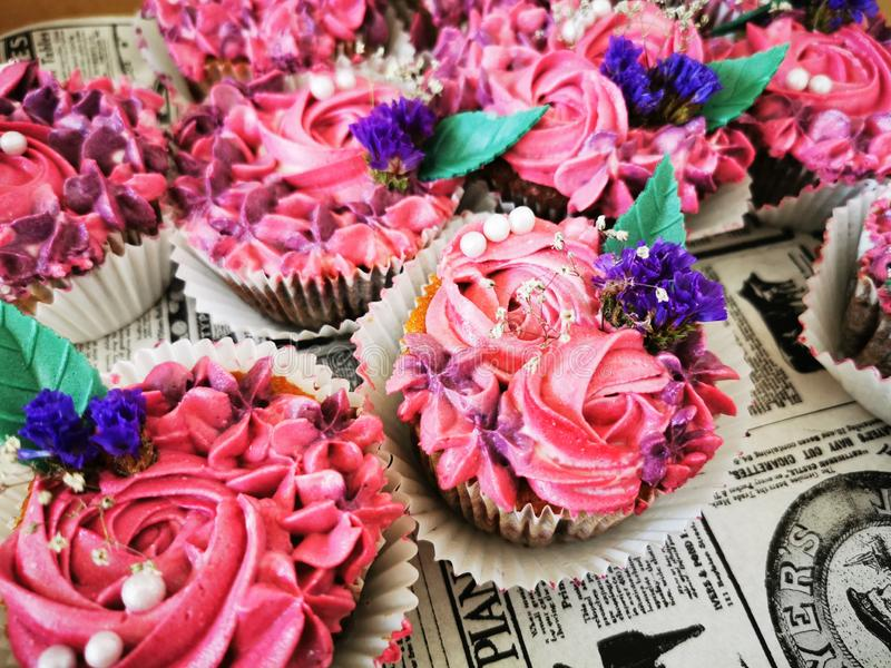 Delicious design cupcakes with flowers. Delicious, cupcakes, flowers, rose, purple, blue, green, leaf, leaves, creative, design royalty free stock images