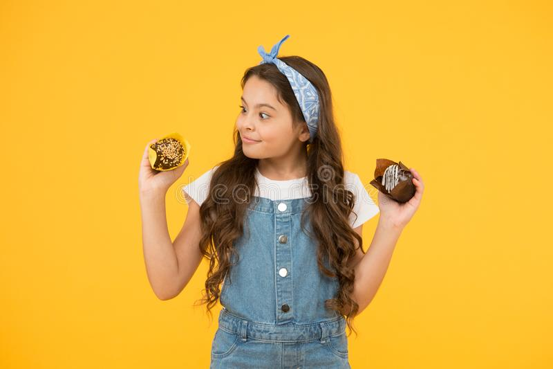 Delicious cupcakes. Happy childhood. Adorable smiling child with cupcakes on yellow background. Cafe restaurant food. Yummy cupcakes. Bakery and confectionery royalty free stock photo