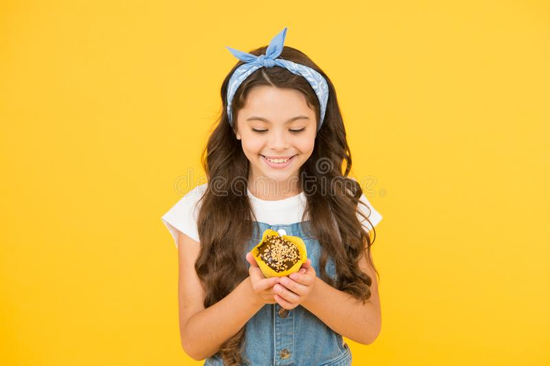 Delicious cupcakes. Little child with muffin on yellow background. Treat someone with sweets. Yummy cupcake. Homemade. Muffin. Happy childhood. Bakery stock image