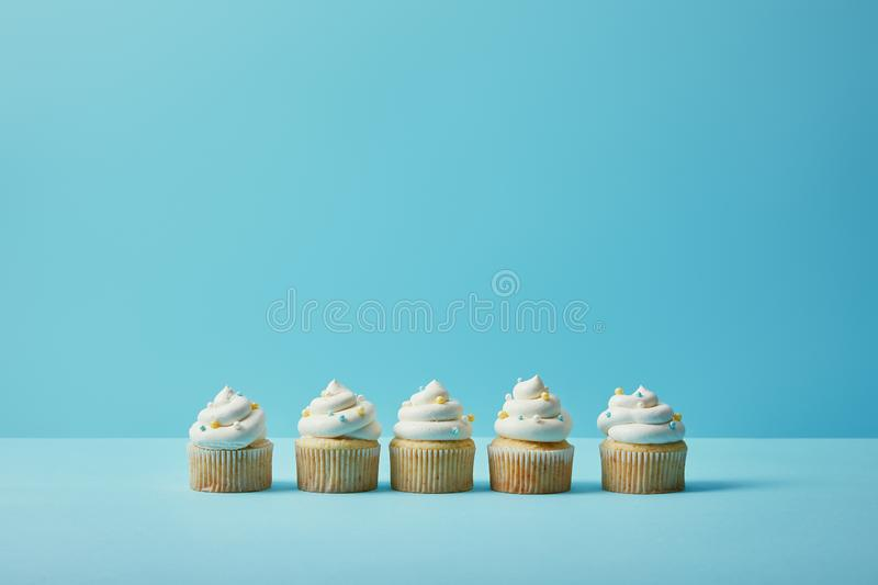 Delicious cupcakes with sugar sprinkles. On blue background royalty free stock image