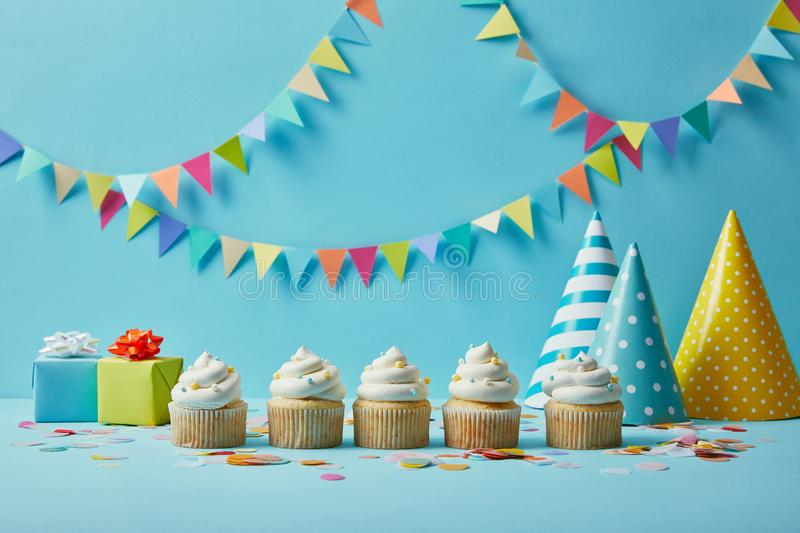 Delicious cupcakes with sugar sprinkles, party hats and gifts on blue background. With colorful bunting royalty free stock photo